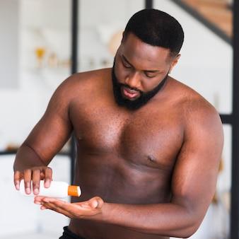 Portret brodaty mężczyzna używa moisturizer