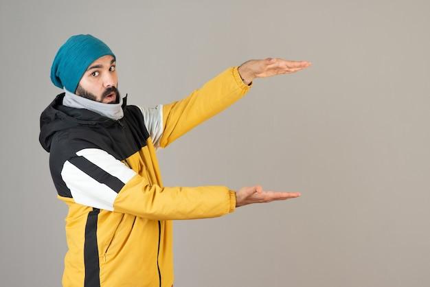 Portret brodaty mężczyzna w ciepłych ubraniach pokazujących rozmiar rękami.