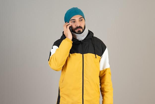Portret brodaty mężczyzna w ciepłych ubraniach rozmawia przez telefon komórkowy.