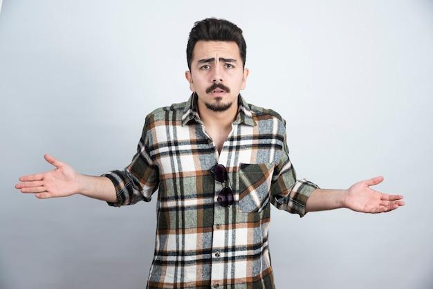 Portret brodaty mężczyzna w okularach pyta, co się dzieje na białej ścianie.
