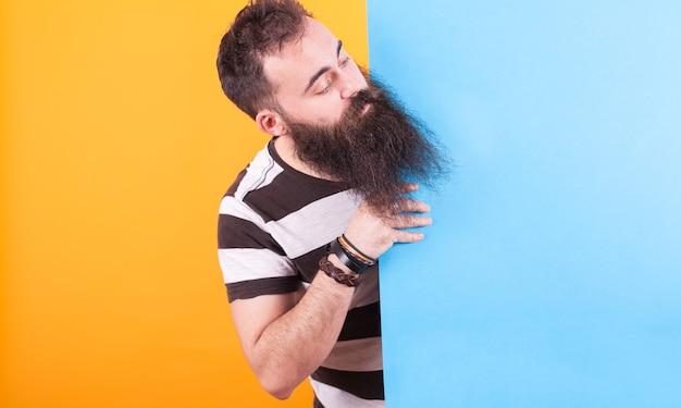 Portret brodaty mężczyzna wystaje głowę za niebieski panel na żółtym tle. przystojny mężczyzna.