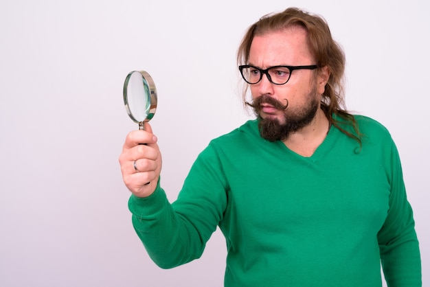 Portret brodaty mężczyzna z nadwagą i długimi włosami na sobie zielony sweter na białej ścianie
