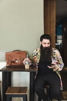 Portret brodaty młody człowiek siedzi w kawiarni przy użyciu telefonu komórkowego