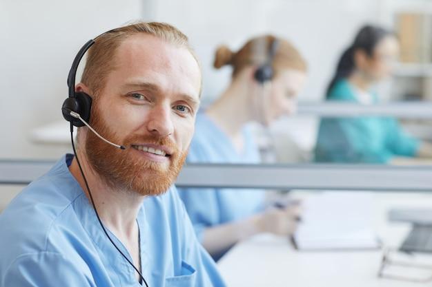 Portret brodaty młody człowiek w słuchawkach uśmiecha się podczas pracy w call center w biurze