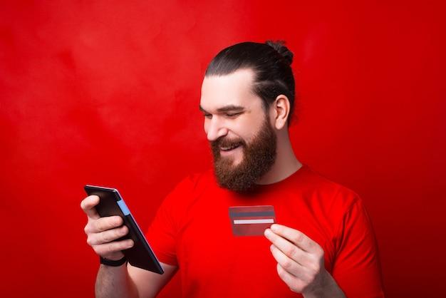 Portret brodaty młody człowiek za pomocą tabletu i płacąc online kartą kredytową