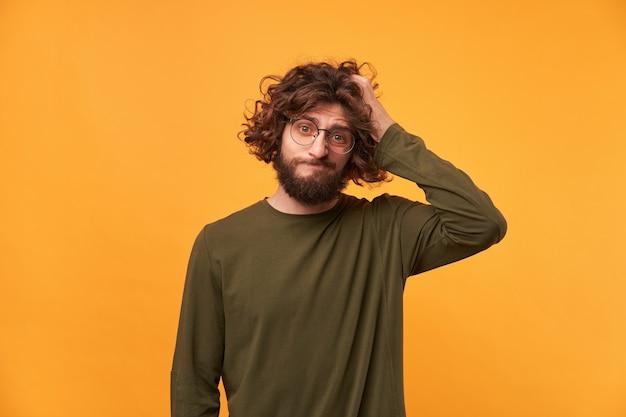 Portret brodaty niedbale ubrany mężczyzna w okularach o ciemnych kręconych włosach