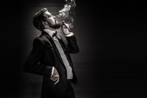 Portret brodaty pan w garniturze, palący cygaro