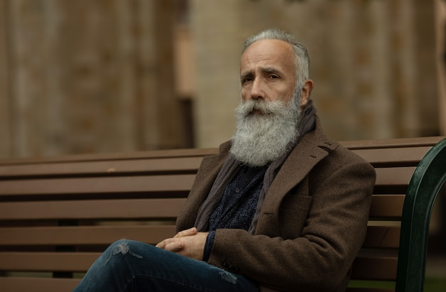 Portret brodaty starszy mężczyzna outdoors, siedzi na ławce w parku.