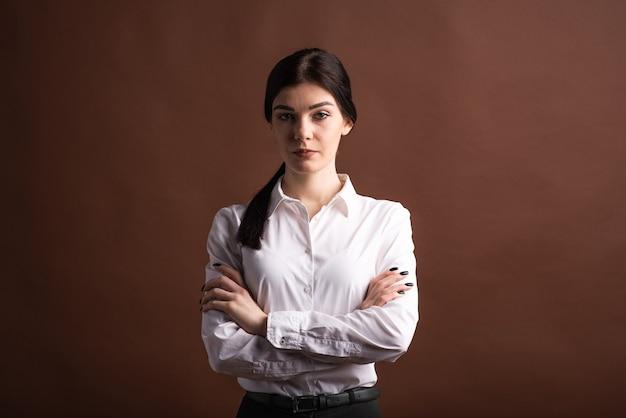Portret brunetka bizneswoman, która skrzyżowała ramiona