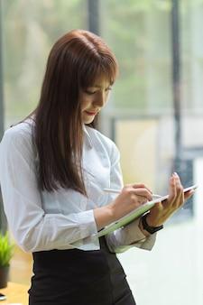 Portret brunetka bizneswoman stoi i koncentruje się na przenośnym tablecie z formalnymi ubraniami