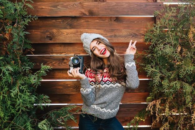 Portret brunetka dziewczyna z długimi włosami w ciepły sweter, zabawy z aparatem na drewnianym zewnątrz.