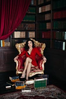 Portret brunetka w czerwieni sukni obsiadaniu na karle przy bibliotecznym wnętrzem.