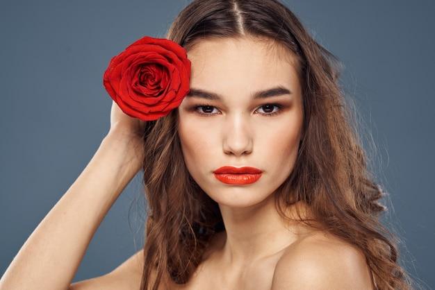 Portret brunetka z czerwoną szminką na ustach, piękna kobieta z różą