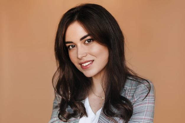 Portret brunetki brązowooka śliczna uśmiechnięta kobieta na beżowej ścianie.