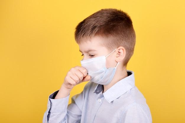 Portret brunetki chłopiec w medycznej masce kaszle.