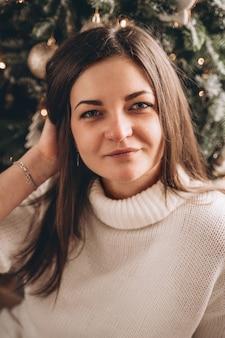 Portret brunetki dziewczyna w białym swetrze w pobliżu choinki
