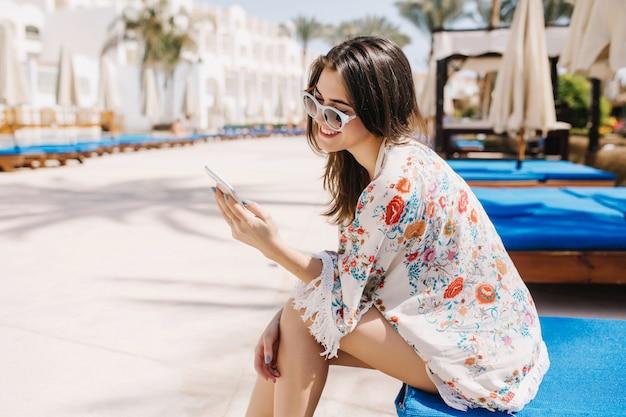 Portret brunetki dziewczyna z prostymi włosami wiadomości tekstowej podczas odpoczynku na letnisku. urocza dama w stroju z kwiatowym nadrukiem i okularami przeciwsłonecznymi siedząca na kanapie w tropikalnym słońcu i uśmiechnięta