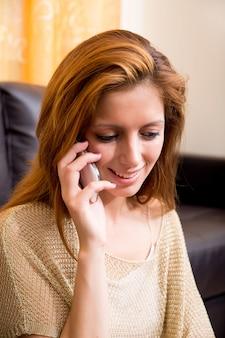 Portret brunetki dziewczyny siedzącej na ziemi, telefonowanie.