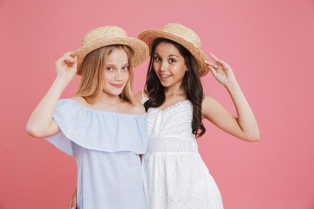 Portret brunetki i blondynki letnie dziewczyny 8-10 ubranych w sukienki pozowanie na kamery dotykając słomkowych kapeluszy z uśmiechem, odizolowane na różowym tle