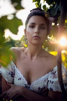 Portret brunetki kobieta w białej sukni stoi w winnicy w lecie we włoszech