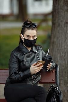Portret brunetki kobieta w czarnym ochronnej maski obsiadaniu na ławce w parku, pogodny wiosna dzień. kobieta rozmawia przez telefon komórkowy