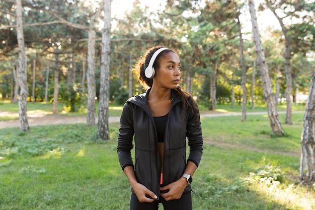 Portret brunetki kobiety 20s na sobie czarny dres i słuchawki, spacerując po zielonym parku