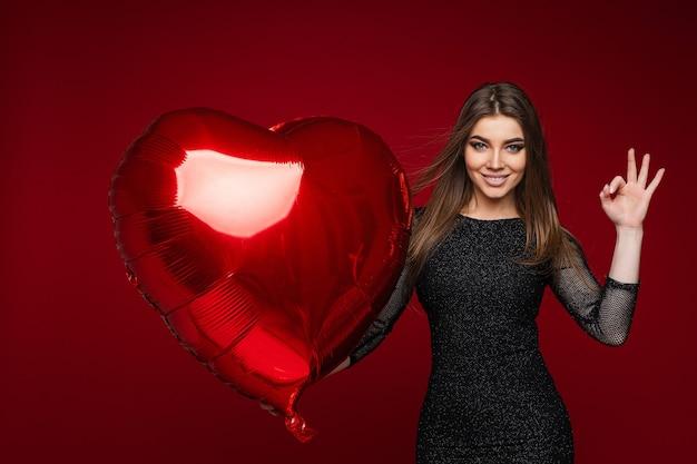 Portret brunetki kobiety rasy kaukaskiej w ciemnej sukience koktajlowej z czerwonym balonem w kształcie serca, czyniąc dobry gest ręką. izoluj na czerwonym tle.