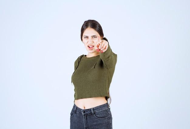 Portret brunetki kobiety stojącej gniewnie i wskazując na kamerę.