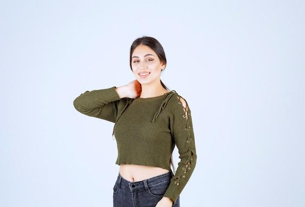 Portret brunetki kobiety stojącej i uśmiechającej się do kamery.