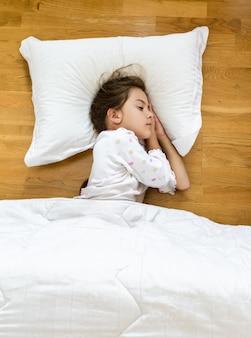 Portret brunetki małej dziewczynki śpiącej na podłodze pokrytej kocem