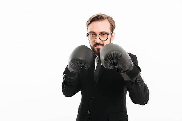Portret brunetki mężczyzna w czarnym kostiumu, eyeglasses i pozować w bokserskich rękawiczkach, odizolowywający nad biel ścianą
