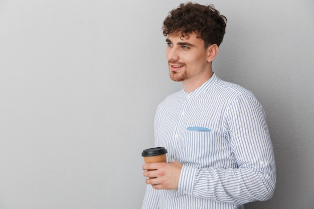 Portret brunetki młodego mężczyzny ubranego w koszulę, uśmiechniętego i pozującego z kawą na wynos w ręku na białym tle nad szarą ścianą