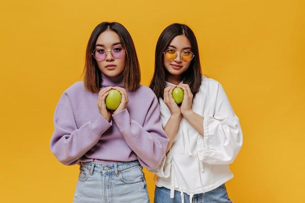 Portret brunetki młodej azjatyckiej dziewczyny w kolorowych okularach przeciwsłonecznych i bluzach trzyma zielone świeże jabłko na izolowanej pomarańczowej ścianie