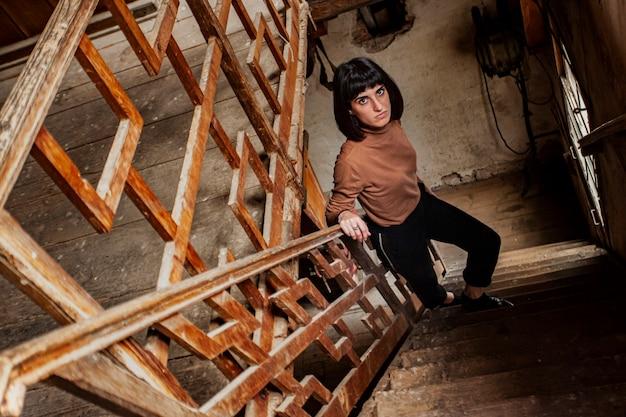Portret brunetki na klatce schodowej opuszczonego domu, obraz w słabym świetle