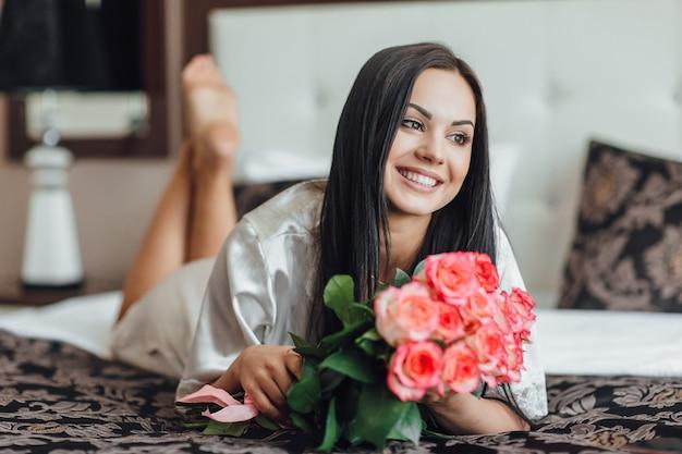Portret brunetki rano w swoim pokoju, który leży na łóżku z bukietem róż w ramionach.