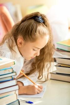 Portret brunetki uczennicy otoczonej książkami odrabiającymi pracę domową