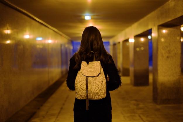 Portret brunetki w przejściu podziemnym z tyłu z białym plecakiem