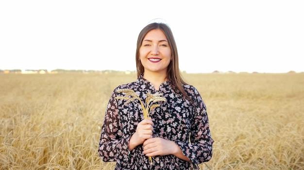 Portret brunetki z bukietem kłosów dojrzałej pszenicy na polu