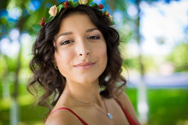 Portret brunetki z kwiatami we włosach w zielonym parku.