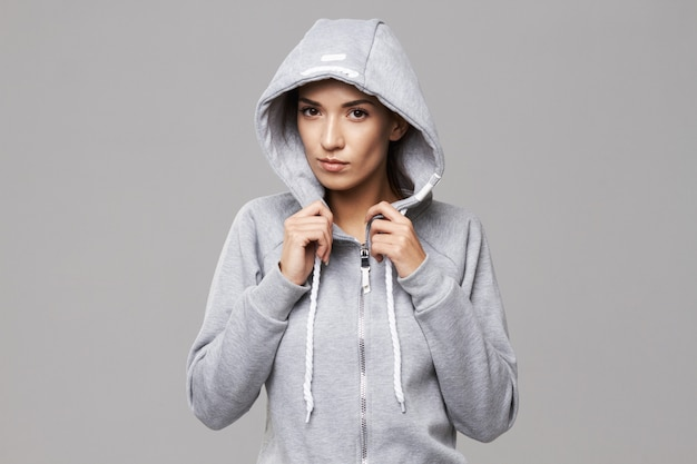 Portret brutalna sportive kobieta w kapiszonie i sportswear na bielu.
