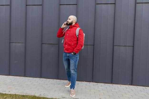 Portret brutalnego faceta z brodą w zwykłym ubraniu, który rozmawia przez telefon na ulicy