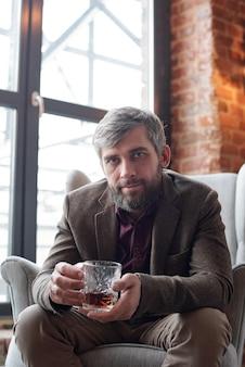 Portret brutalnego mężczyzny w średnim wieku w kurtce, siedzącego w wygodnym fotelu i samotnego picia whisky