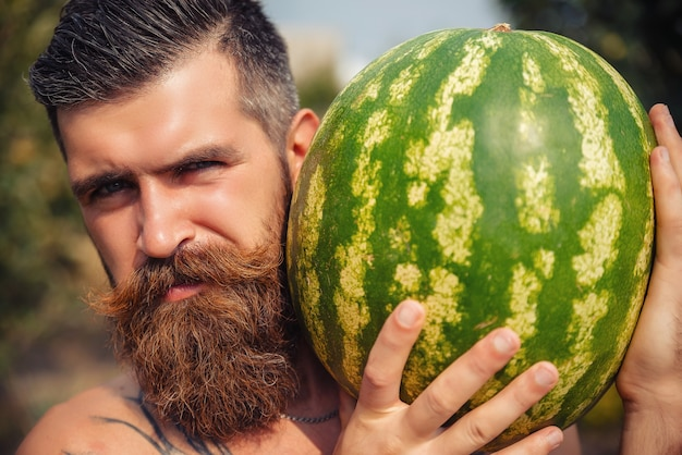Portret brutalnego mężczyzny z wąsami i czerwoną brodą bez koszulki z nagim torsem trzymającym dużego dojrzałego arbuza