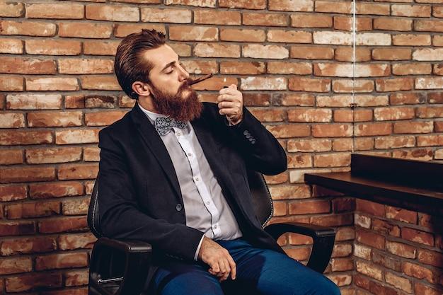 Portret brutalnego seksualnego przystojnego mężczyzny siedzącego na krześle i podpalającego cygaro na tle ceglanego muru. koncepcja ognia