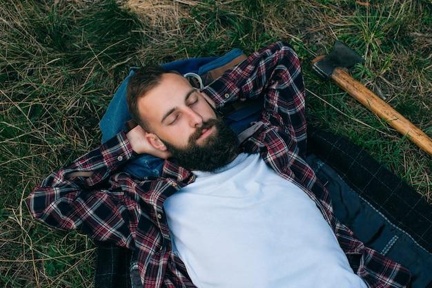 Portret brutalny, brodaty i wąsaty drwal hipster cygan w lesie z siekierą. człowiek leżący na trawie i marzenia