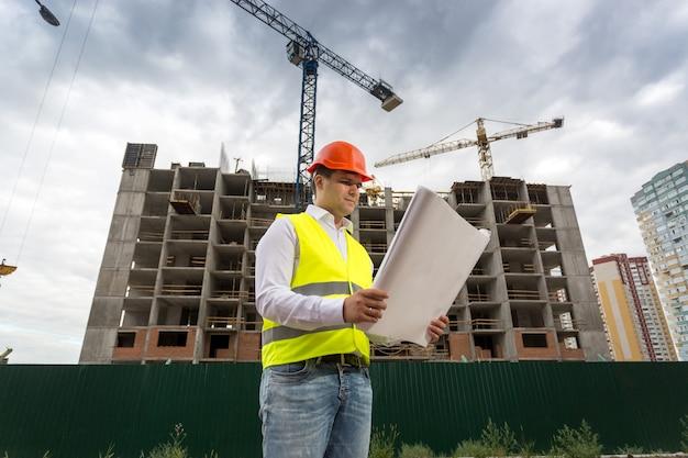 Portret brygadzisty patrzącego na plany na placu budowy