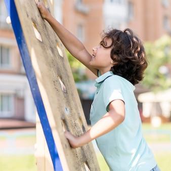 Portret buźkę chłopiec wspinaczka