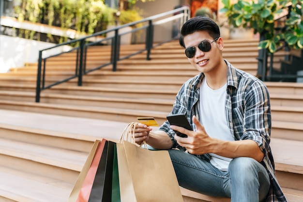 Portret buźkę młody przystojny mężczyzna w okularach przeciwsłonecznych trzyma papierową torbę