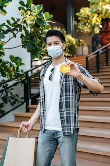 Portret buźki młody przystojny mężczyzna w masce, trzymający papierową torbę