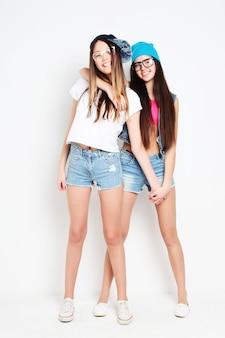 Portret całego ciała dwóch szczęśliwych dziewczyn hipster na białym tle